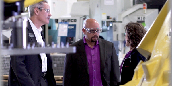 Two men and a woman with safety glasses on in an industrial setting