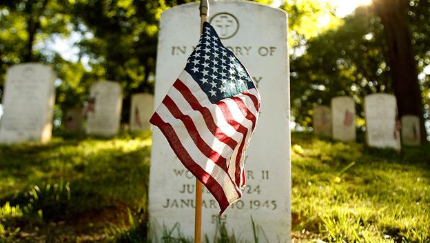 Small American flag in front of a tombstone on a sunny day