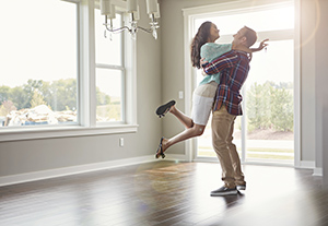 Man holding woman in the air in an empty house on a sunny day