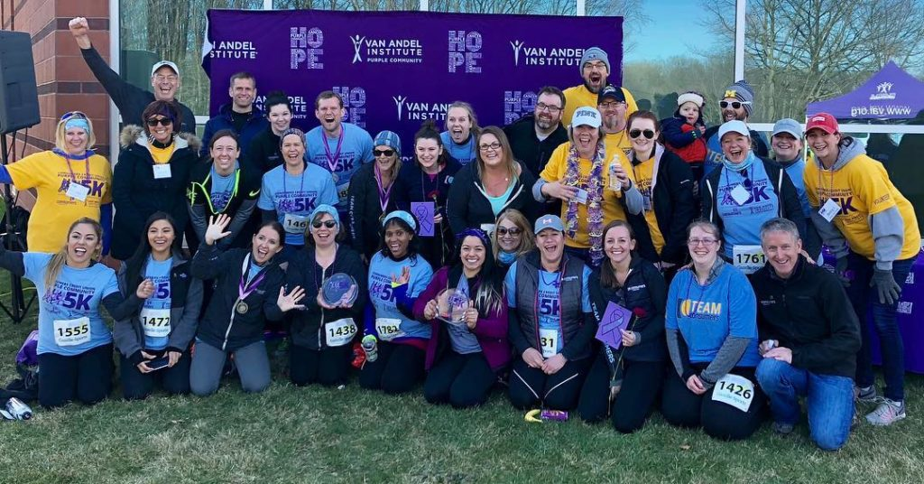 Large group of runners smiling at a 5K benefit run
