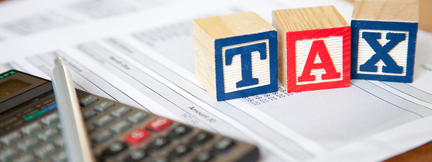"""Calculator, pen, and tax documents with red and blue building blocks that spell out """"tax"""""""