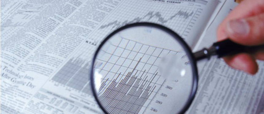 Magnifying glass over a bar graph in the financial news section of a newspaper