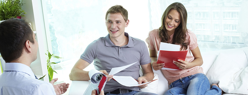 Young couple perusing paperwork and conversing with another man