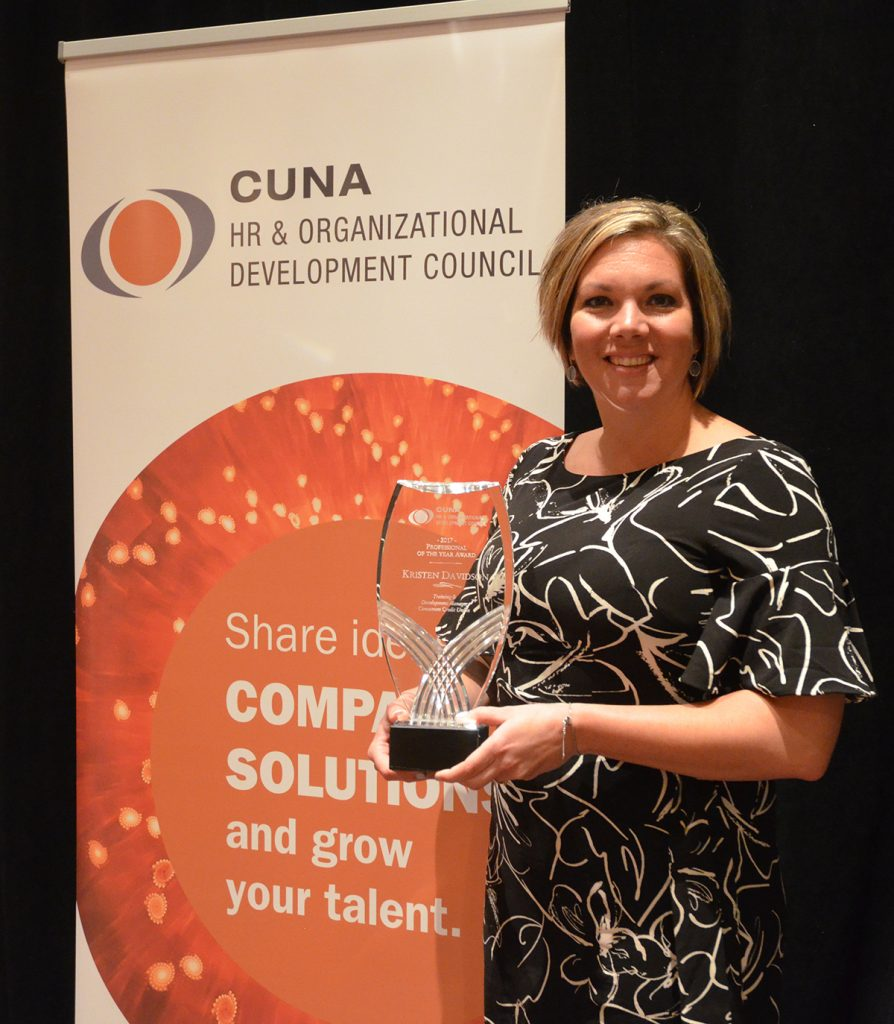 Woman in a black and white dress holding an award for the CUNA HR and Organizational Development Council