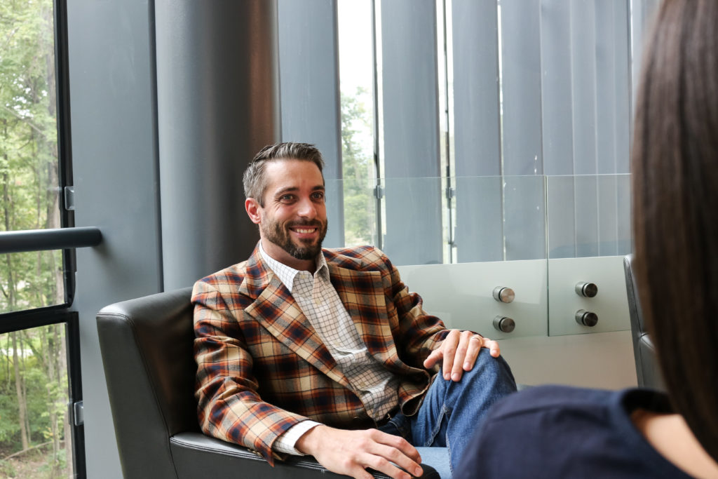 Man wearing a plaid sport coat sitting in an black armchair smiling
