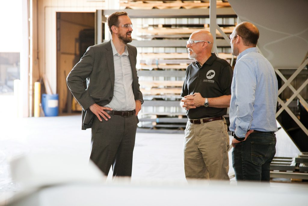 Three men wearing safety glasses in a warehouse conversing with each other