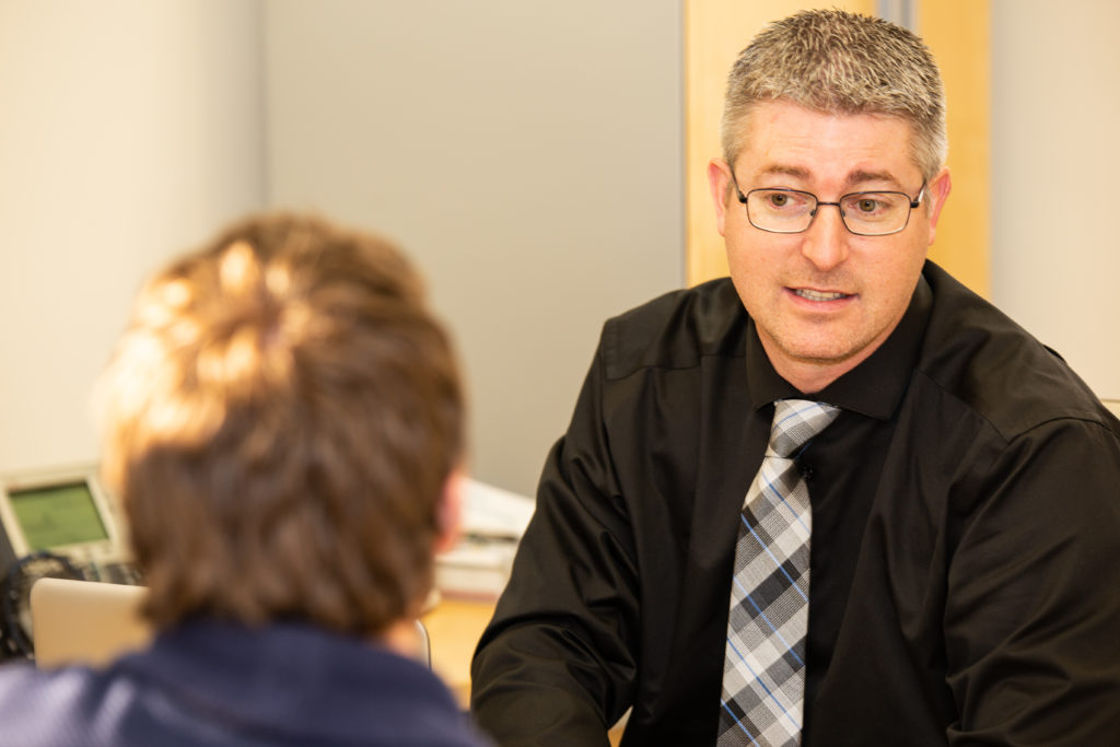 Man with glasses and a tie speaking with another man in an office setting