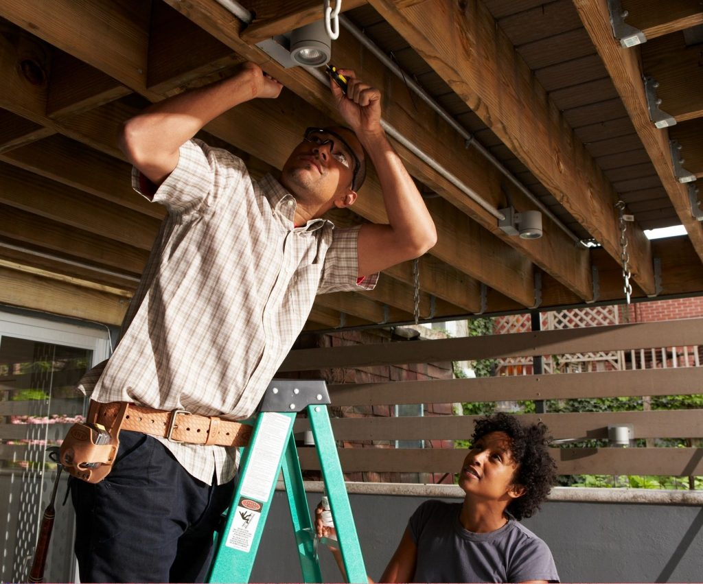 Man on a ladder installing track lighting under a deck with a woman