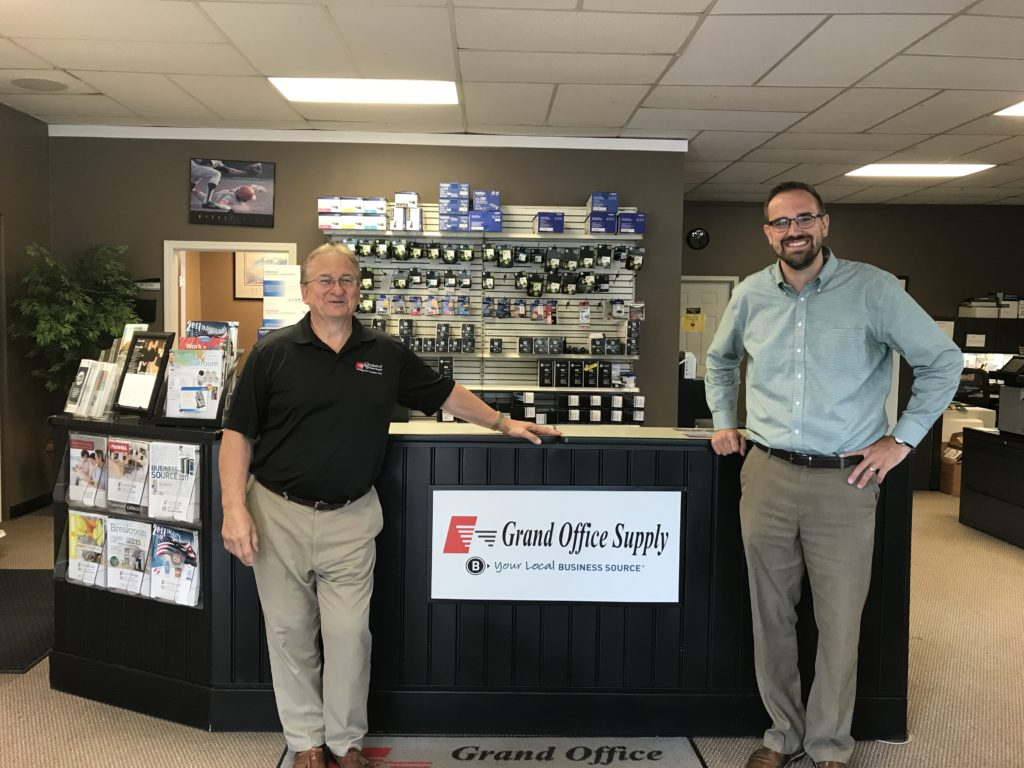Two men standing at the checkout counter of an office supply store