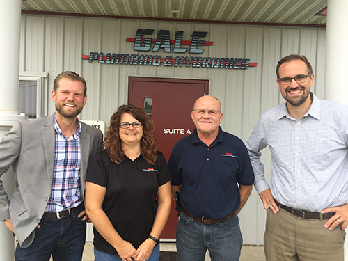 Three men and a woman smiling and posing for a picture in front of the Gale Plumbing and Hydronics business locations
