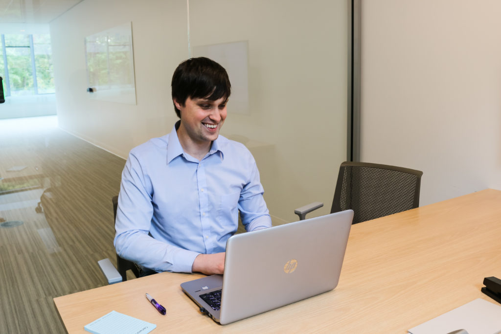 Young man wearing a light blue button down shirt sitting at a table working on a laptop while smiling