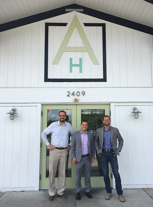 Three men standing outside of a business storefront
