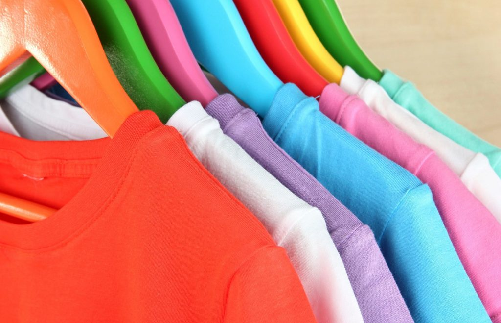 An array of colorful t-shirts hanging on colorful hangers