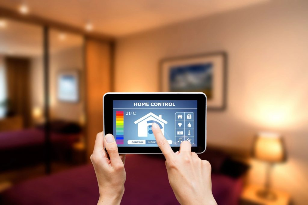 A pair of hands using a remote app to adjust their home temperature