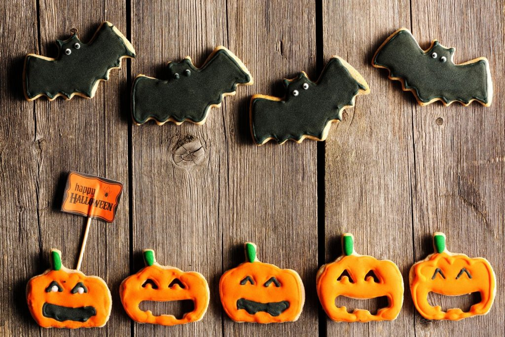 Four black bat cookies and five jack-o'-lantern cookies laid out on wooden slats