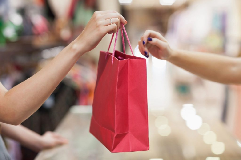 A woman handing a red gift bag to a customer in a store