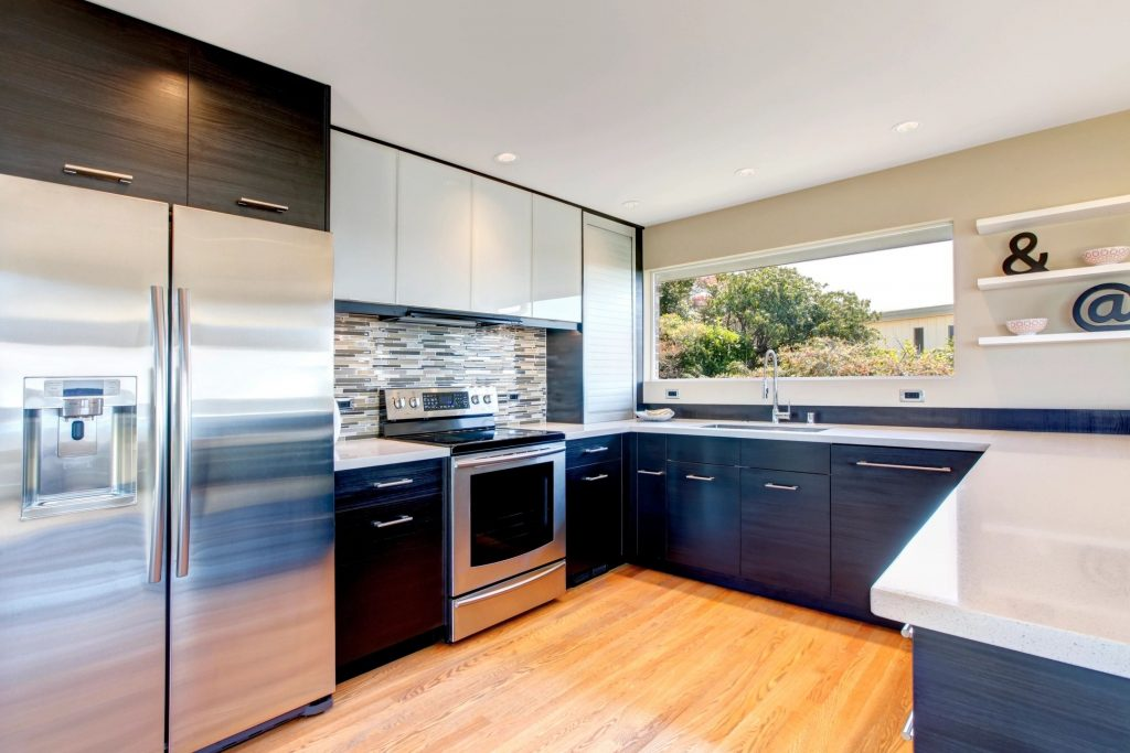 A newly renovated kitchen with hardwood floors and white countertops