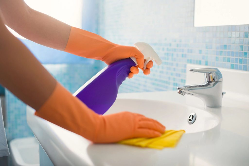A close-up of a person with orange rubber gloves with spraying cleaner on a bathroom sink