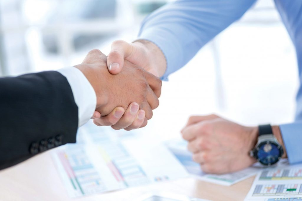 Close-up of two men shaking hands over a desk covered in spreadsheets