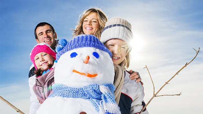 A family posing behind a snowman on a sunny winter day