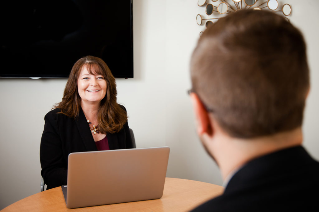 A woman in a meeting with a man with a laptop in front of her