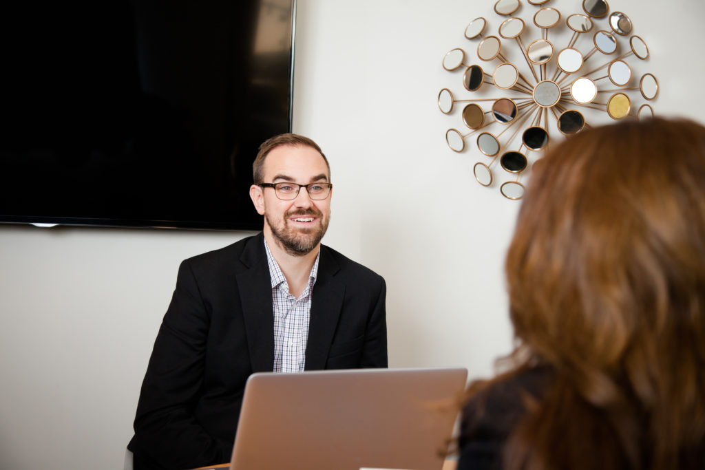 A bearded man in front of a laptop in a meeting with a woman