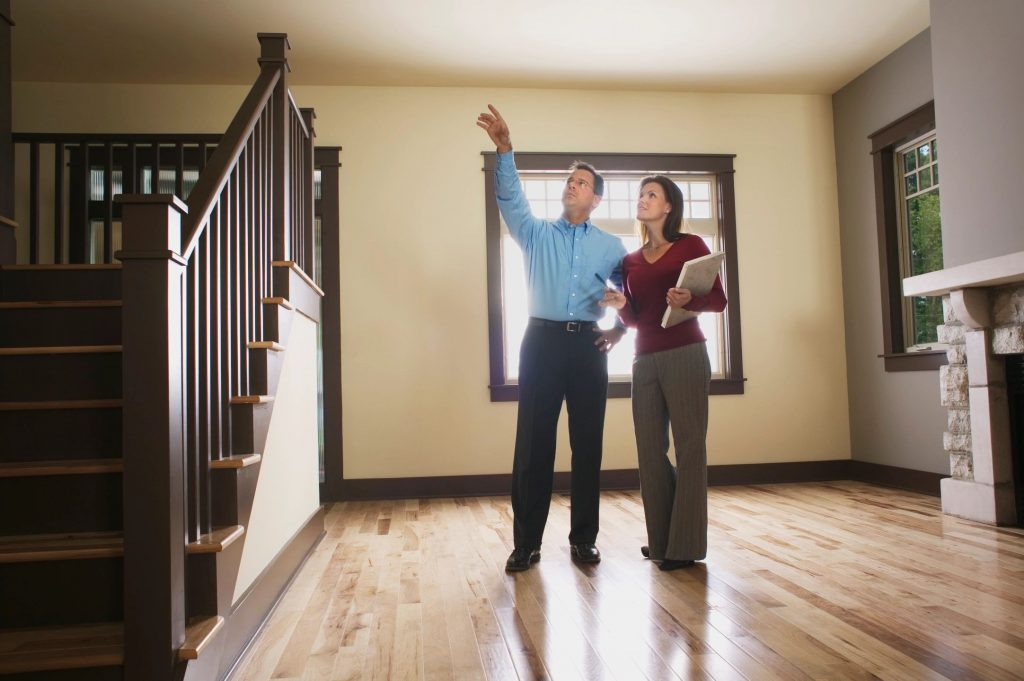 A man and woman standing in an empty living room discussing the house