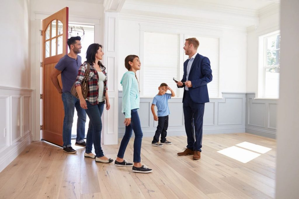 A family walking into an empty home with a real estate agent