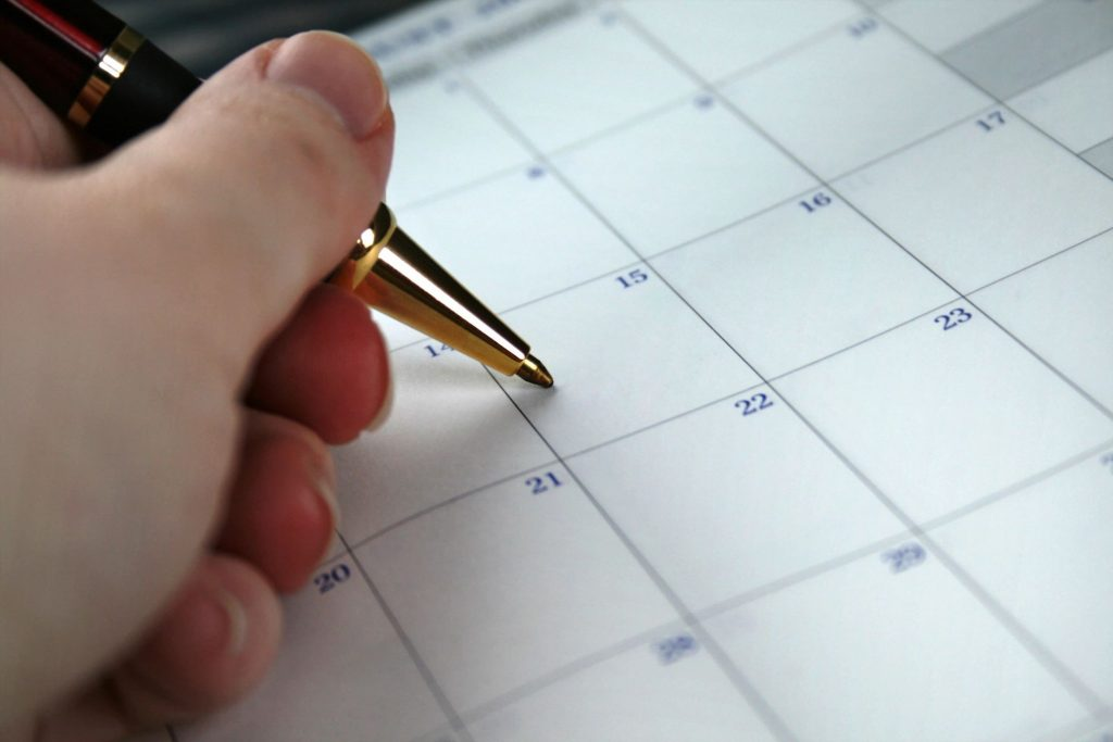 Close-up of a hand holding a pen on top of a calendar