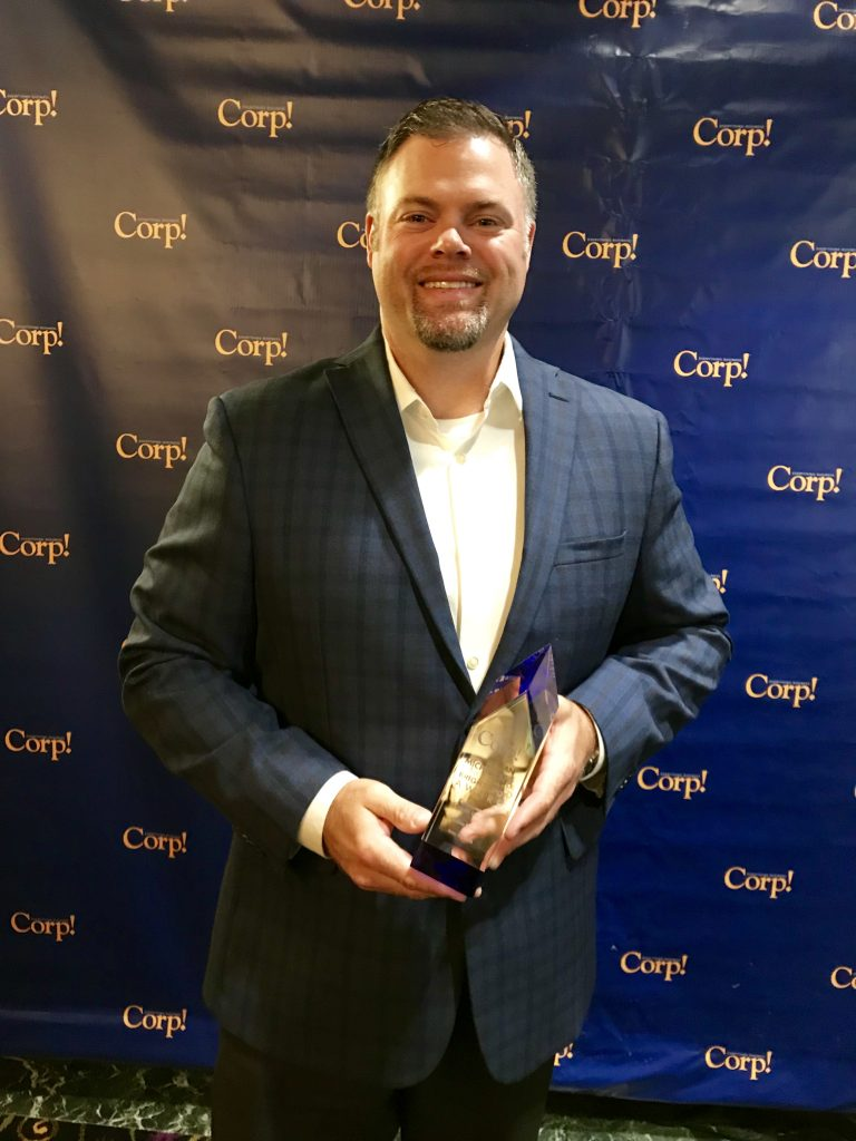 A man smiling holding an award in front of a step-and-repeat at a Corp! event