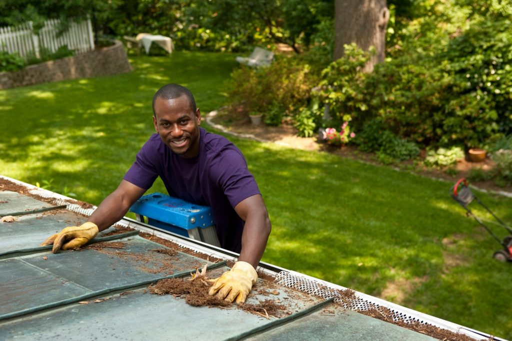 A man on a ladder cleaning leaves and pine needles off a metal roof and a gutter