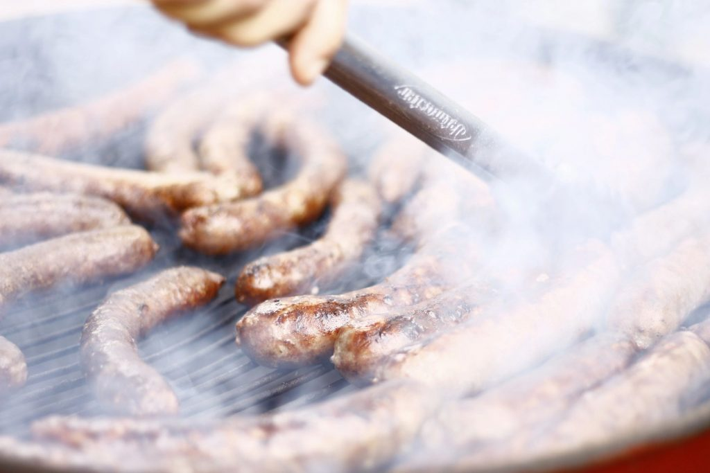 Close-up of someone grilling sausages with lots of smoke rising off of the grill