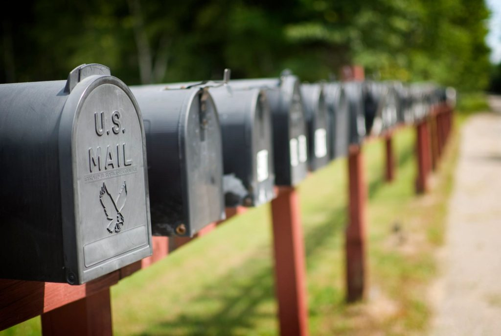 A row of black mailboxes on a sunny day