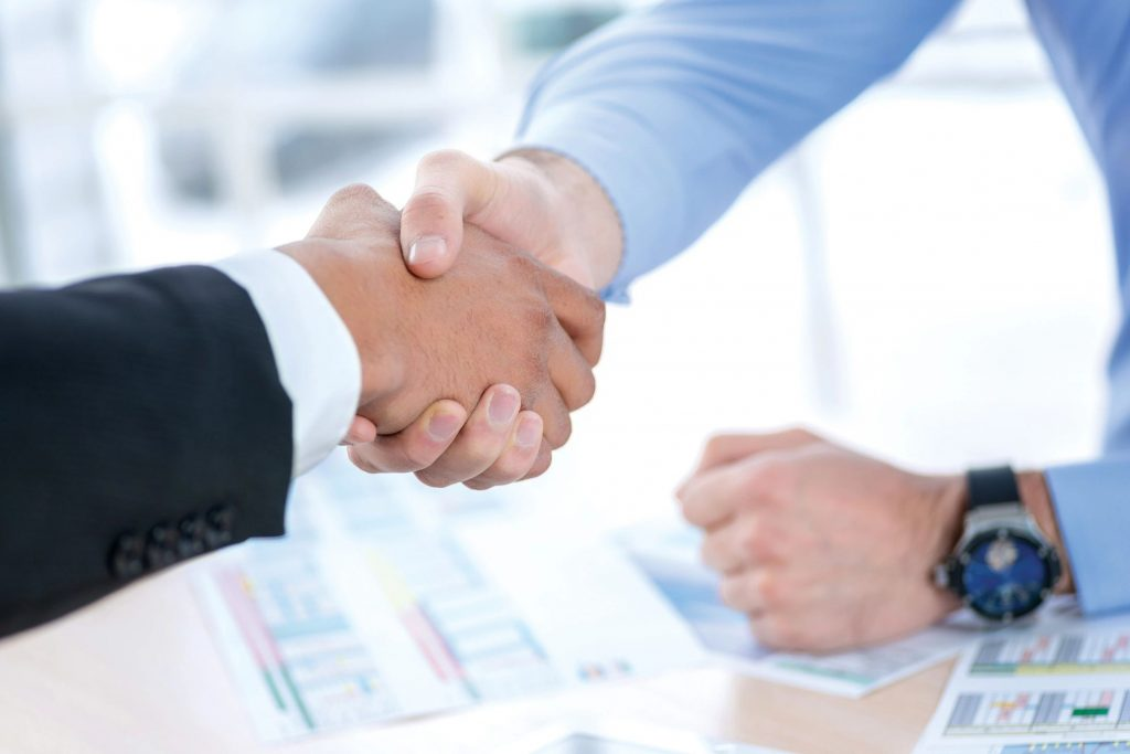 Close-up of a two men shaking hands over graphs and spreadsheets