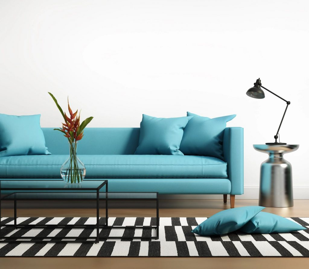 A turquoise couch with a glass coffee table next to a lamp with two pillows on the ground