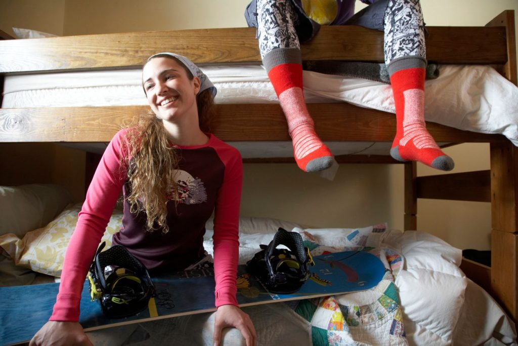A girl with wearing a bandana sitting on a bottom bunk of a bunk bed with a snowboard across her lap