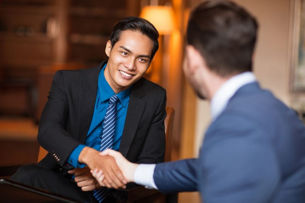 Two young men in suits shaking hands in an office