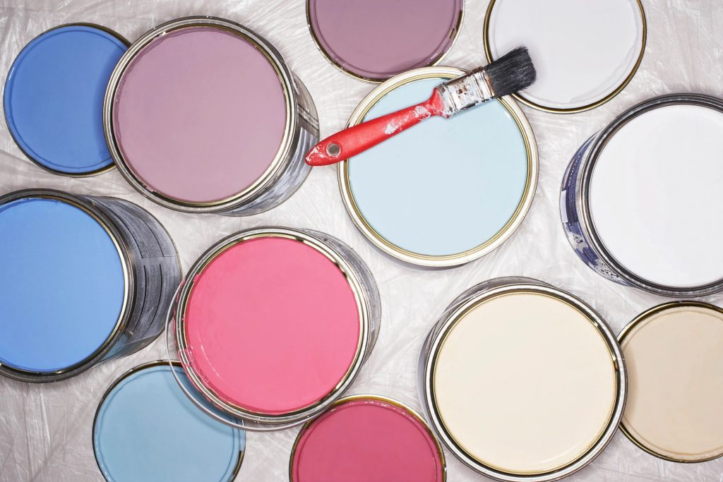 Many paint cans of red, blue, purple, and white open with a red paintbrush resting on one