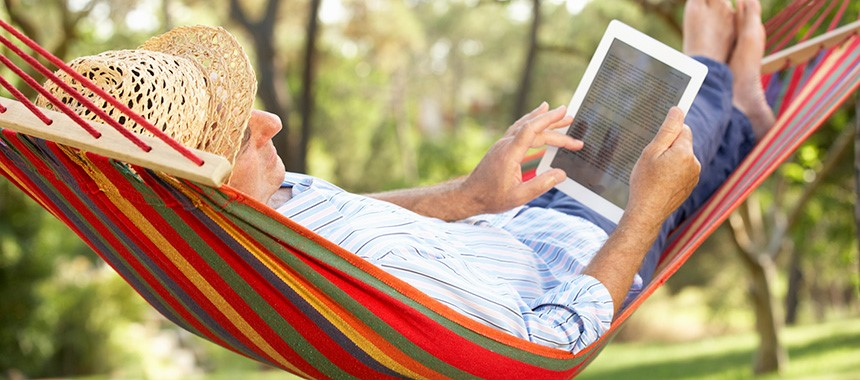 A man with a sun hat laying on a colorful stripe hammock while using a tablet