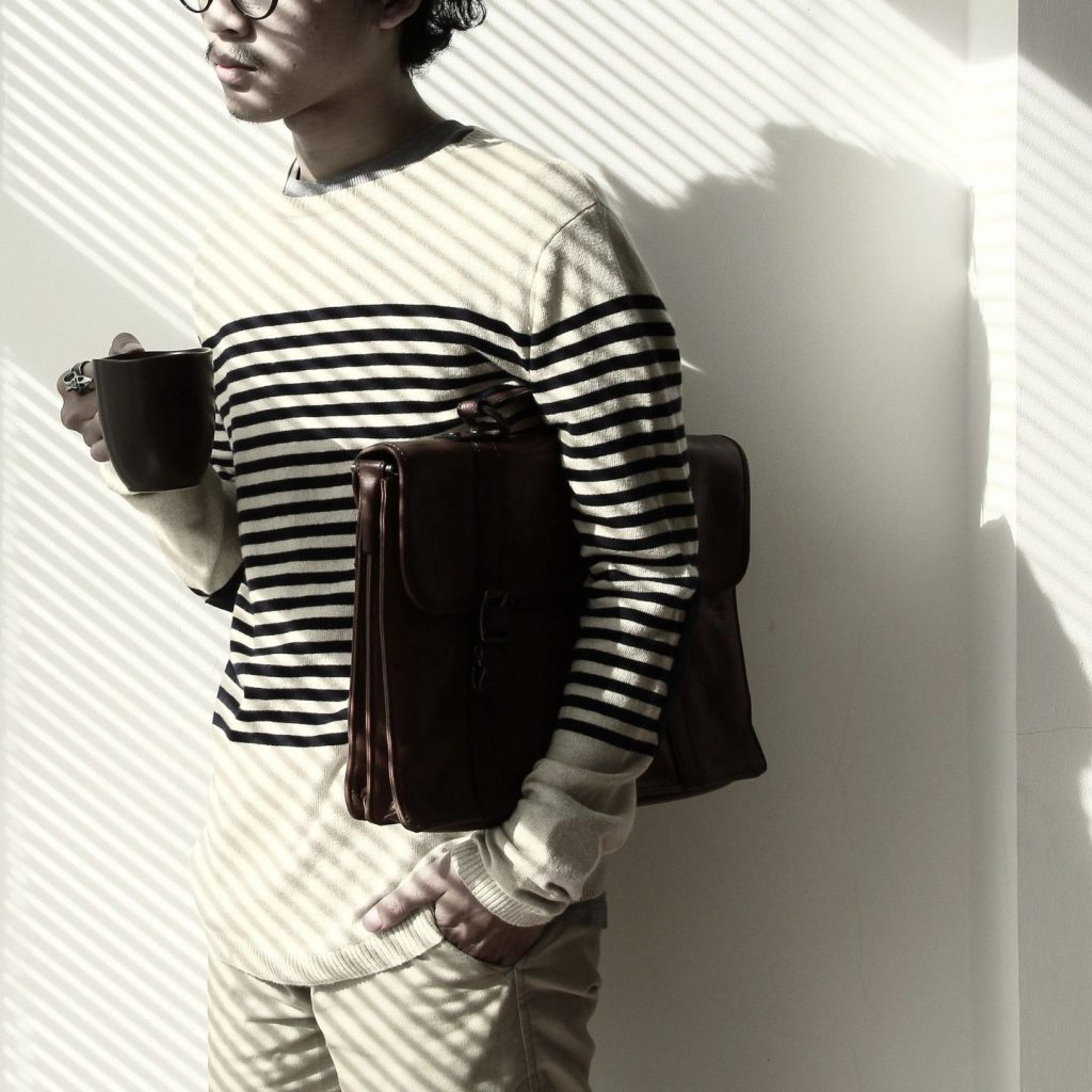 A young man standing against a white wall holding a coffee cup with a briefcase under his arm wearing a striped sweater