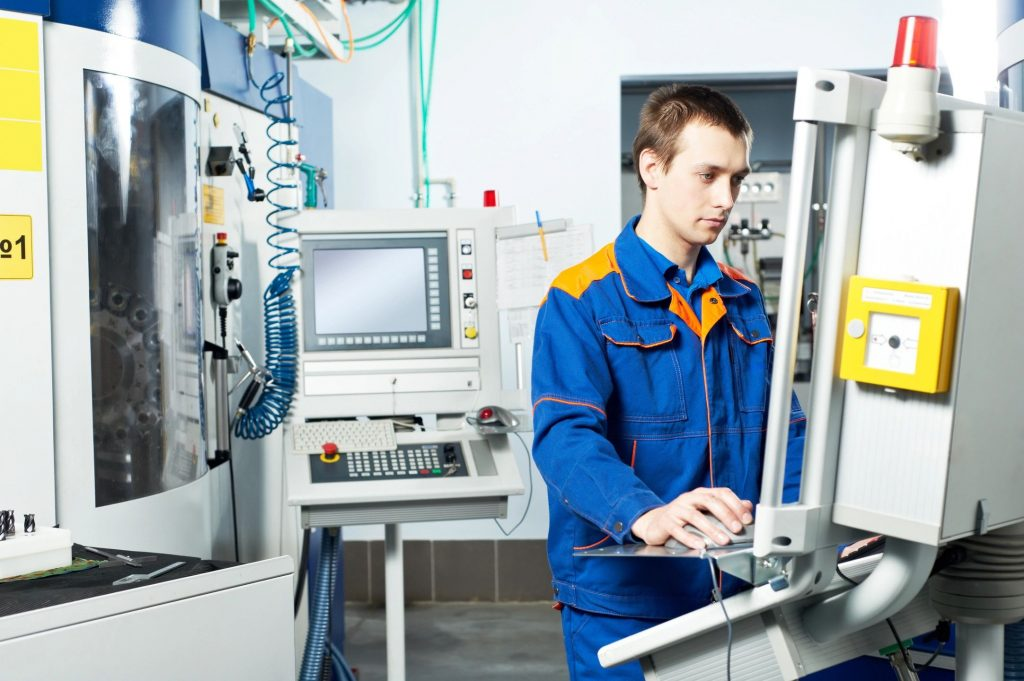 A young man working on a machine in a robotics lab