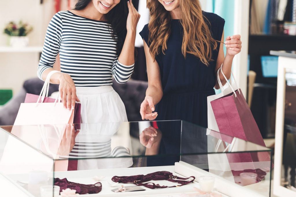 Two young ladies holding shopping bags while looking a glass display case in a store