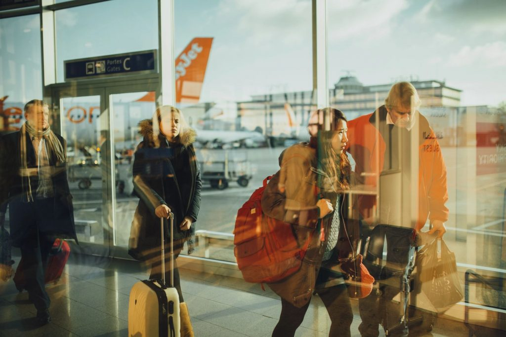 Travelers walking through an airport terminal with their luggage