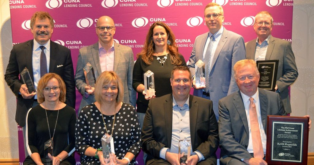 A group of men and women posing with awards in front of a CUNA Leading Council Step-and-Repeat