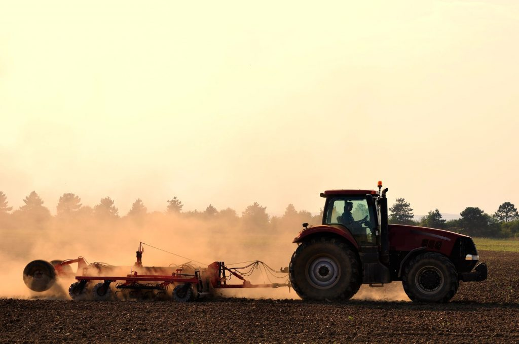 A tractor pulling a tillage attachment on the back kicking up dust on a farm