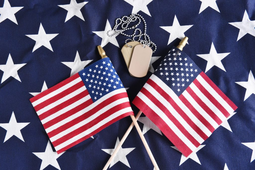 Two small American flags criss-crossed near a set of dog tags on the stars section of a larger American flag