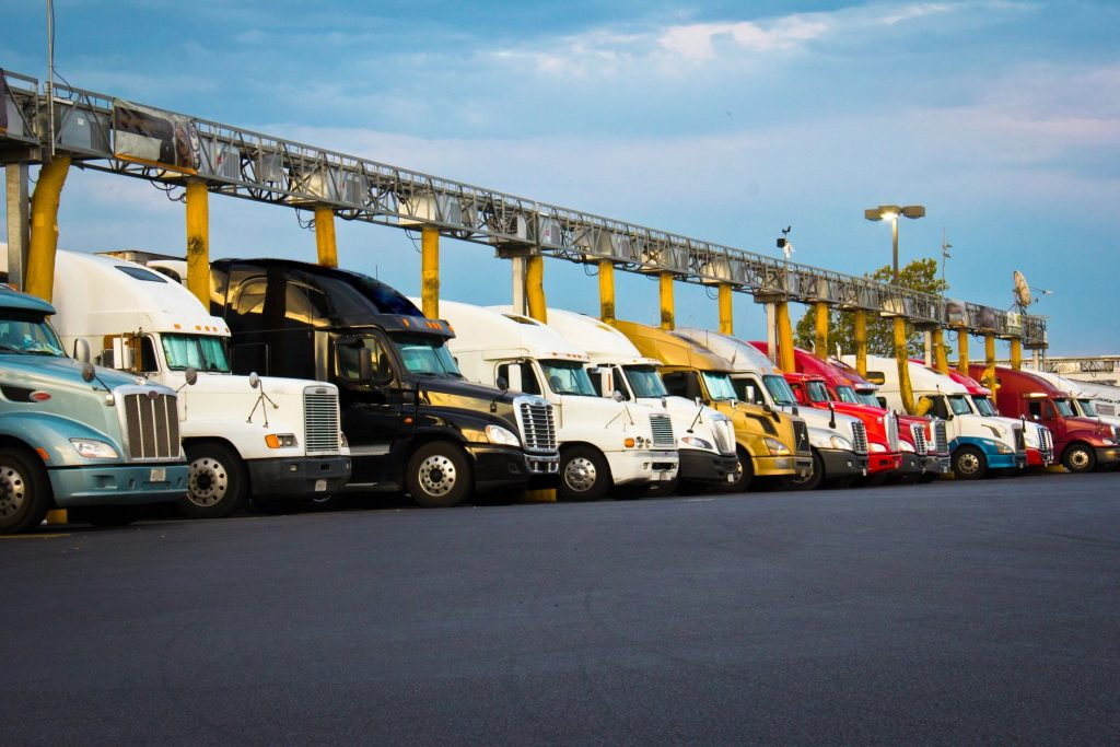 A fleet of commercial semi trucks in a line on a partly cloudy day
