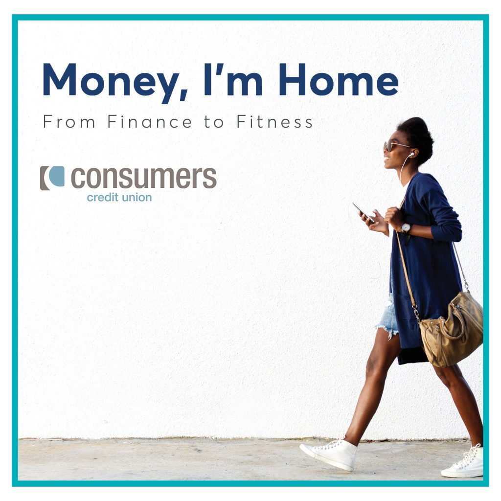 A woman walking and listening to a pair of earbuds in front of a white wall with the Consumers Credit Union logo