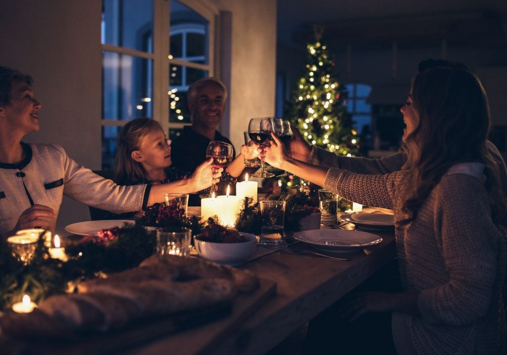 A happy family clinking glasses during a Christmas season dinner at a candle-lit table