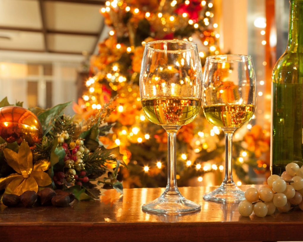 Two glasses of white wine in front of a lit-up Christmas tree